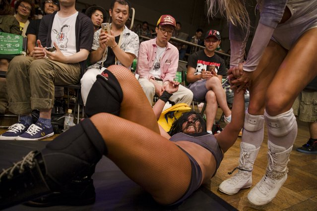 Members of the audience watch female wrestlers fight outside of the ring during a Stardom female professional wrestling show at Korakuen Hall in Tokyo, Japan, July 26, 2015. (Photo by Thomas Peter/Reuters)