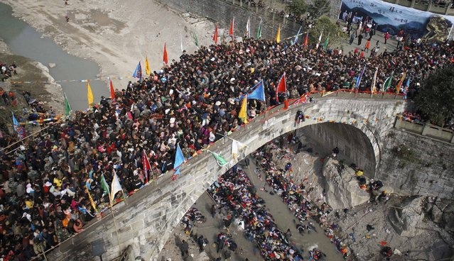 People crowd onto a bridge during the annual Caiqiaohui event in Mianyang, Sichuan province, March 18, 2014. People believe that by stepping onto the bridge during the three-day spring event can help them escape tribulations and illnesses. (Photo by Reuters/Stringer)