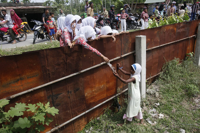 School children hand out food to a Rohingya young girl from outside the fence of a temporary shelter in Bayeun, Aceh province, Indonesia, Thursday, May 21, 2015. In the past three weeks, thousands of people  fleeing persecution in Myanmar and Bangladeshis trying to escape poverty have landed in overcrowded boats on the shores of Indonesia, Malaysia and Thailand. (Photo by Binsar Bakkara/AP Photo)