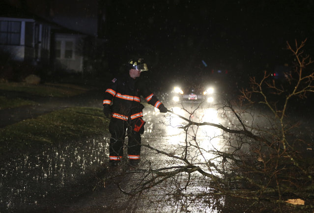 A firefighter removes fallen tree branches from the road in Ottawa, Ill., on Tuesday, February 28, 2017. Tornadoes touched down in the upper Midwest and northern Arkansas on Tuesday, in a spring-like storm system. (Photo by Nuccio DiNuzzo/Chicago Tribune via AP Photo)