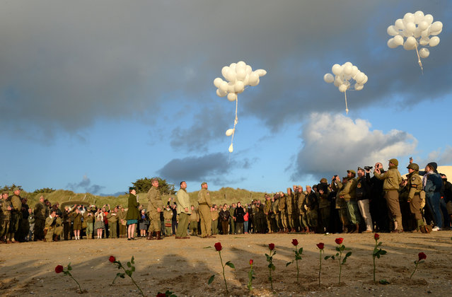 French WWII enthousiasts of the group Overlord 76 plant red roses in the sand and release white balloons in tribute of dead Americans on Utah Beach in Sainte-Marie-du-Mont, northwestern France, on June 6, 2019, during the D-Day commemorations marking the 75th anniversary of the World War II Allied landings in Normandy. (Photo by Jean-Francois Monier/AFP Photo)