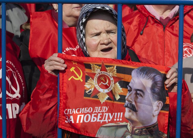 An elderly Russian Communist party supporter holds up a portrait of Soviet dictator Josef Stalin with a Soviet Union sign during a rally in support of Crimea joining Russia near the Red Square in Moscow, Russia, on Saturday, March 22, 2014. Moscow on Friday formally sealed Crimea's annexation, less than a week after a referendum where Crimeans overwhelmingly voted to join Russia. (Photo by Alexander Zemlianichenko Jr/AP Photo)