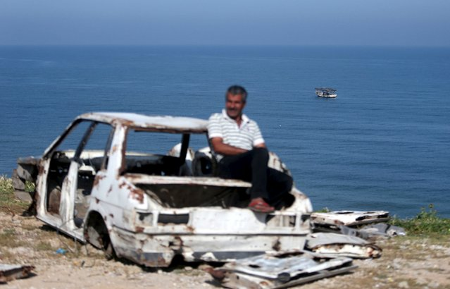A Palestinian man sits on a wrecked car as fishermen ride a boat in the Mediterranean Sea off the coast of Gaza City April 3, 2016. (Photo by Ibraheem Abu Mustafa/Reuters)
