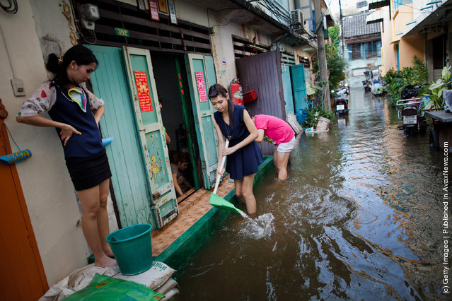 Thai residents scoop water out of their homes on a flooded street in China Town near to to the overflowing Chao Phraya river