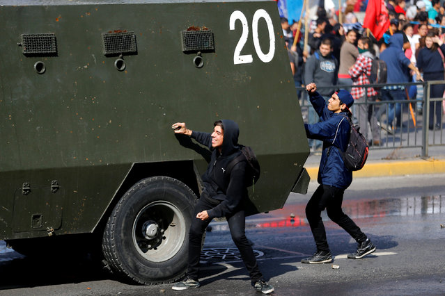Student protesters hit a riot police vehicle during a demonstration to demand changes in the education system in Santiago, Chile, April 21, 2016. (Photo by Ivan Alvarado/Reuters)