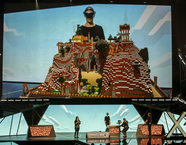 """Microsoft Studios executive Saxs Persson demonstrates how the HoloLens is used to play """"Minecraft"""" at the Xbox E3 2015 briefing ahead of the Electronic Entertainment Expo at the University of Southern California's Galen Center on Monday, June 15, 2015 in Los Angeles. While the audience saw Persson stare at an empty table, a special camera allowed them to see what he was seeing - a perfect 3-D representation of a pixelated """"Minecraft"""" world. (AP Photo/Damian Dovarganes)"""