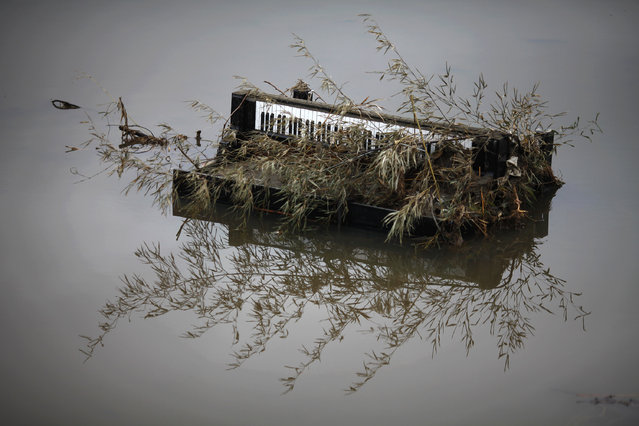 A piano is submerged in water in the area devastated by tsunami in Rikuzentakat March 21, 2011. (Photo by Damir Sagolj/Reuters)
