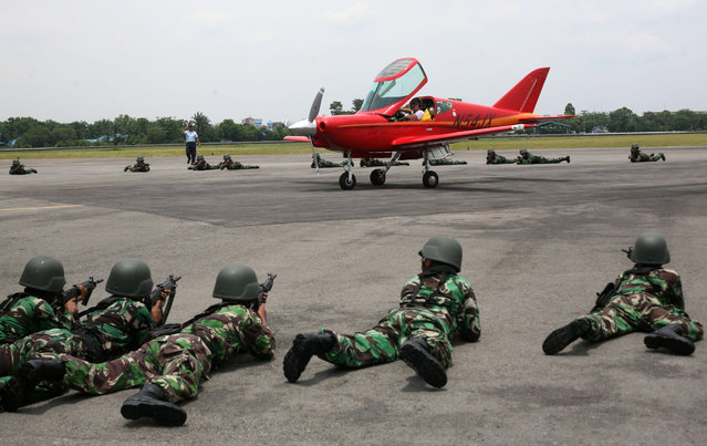Indonesian soldiers train their weapons at an airplane piloted by 65 year-old Heinz Peier of Switzerland after it was intercepted by Indonesian jet fighters and forced to land at Soewondo Air Base in Medan, North Sumatra, Indonesia, Thursday, April 10, 2014. Peier was on a ferry flight from Colombo to Singapore when he entered Indonesian airspace illegally, an Air Force official said.  (Photo by Binsar Bakkara/AP Photo)