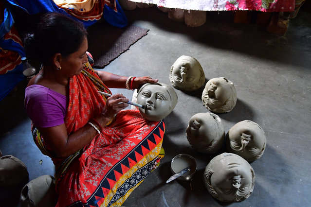 Manju Saha, an idol maker, prepares faces of Durga before an annual festival celebrating the Hindu goddess in Agartala, India on July 21, 2019. (Photo by Abhisek Saha/Barcroft Media)