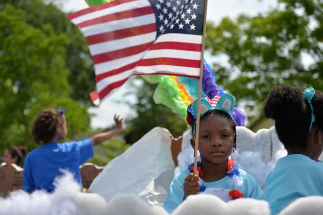 A young girl waves a flag while riding Rice Creek School's float during the Stand Up For America Parade Saturday, April 30, 2016, in Port Wentworth, Ga. (Photo by Josh Galemore/Savannah Morning News via AP Photo)
