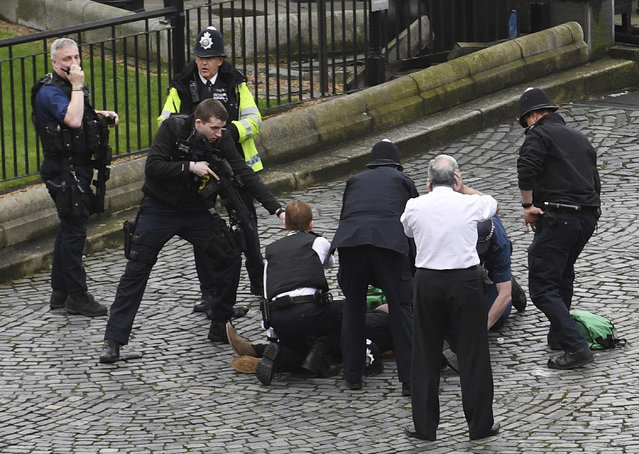 A policeman points a gun at a man on the floor as emergency services attend the scene outside the Palace of Westminster, London, Wednesday, March 22, 2017. (Photo by Stefan Rousseau/PA Wire via AP Photo)