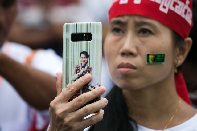 A woman holding a mobile phone with an image of Myanmar's State Counsellor Aung San Suu Kyi takes a video during a protest in support of amendments to the 2008 Myanmar Constitution in Yangon on July 17, 2019. (Photo by Sai Aung Main/AFP Photo)