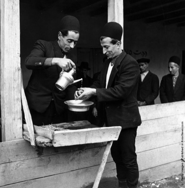 1950:  Two men perform the customary handwashing ceremony at a traditional Muslim wedding in the Mazanderan province of Iran