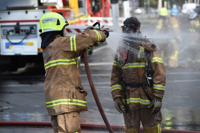 A firefighter is rinsed off at the scene of a fire at the Annunciation of Our Lady Greek Orthodox Church in Melbourne, Australia, 02 May 2016. According to reports, some 200 people were evacuated from nearby buildings during the incident. The fire was under control within an hour, media added. (Photo by Julian Smith/EPA)