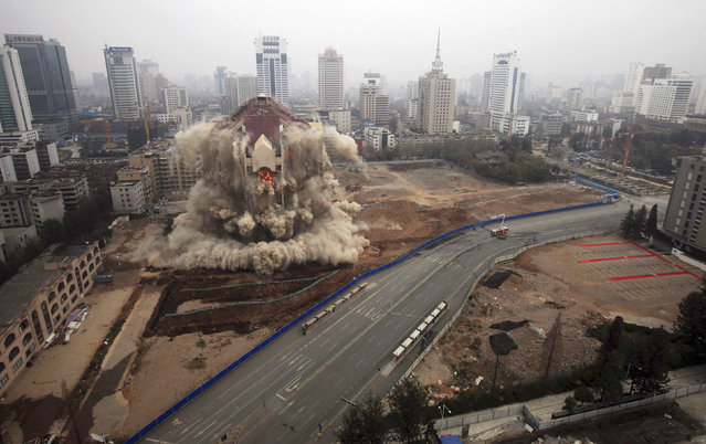 The former Kunming city hall topples during a controlled demolition in Kunming, Yunnan province, China, December 25, 2011. (Photo by Reuters/China Daily)
