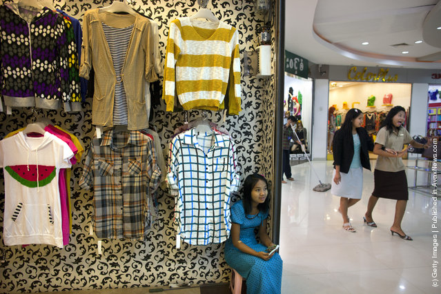 A Burmese woman waits for business at a shop inside a shopping mall
