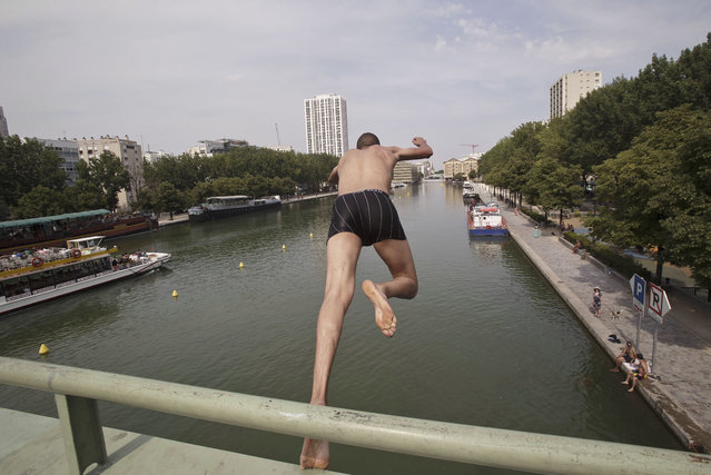 A man jumps from a bridge into the canal of Ourcq in Paris, France, Friday, July 3, 2015. (Photo by Michel Euler/AP Photo)