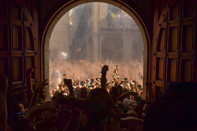"Revelers try to enter in City Hall at the end of the ""Cipotegato"", in the small village of Tarazona, northern Spain, Tuesday, August 27, 2019. Following a tradition coming from at least the middle of the XVIII century, thousands of people gather every year at midday in Tarazona's main square waiting to throw tomatoes at the Cipotegato character, that represents two characters, one of them, a prisoner from the local jail that was given the chance to escape to freedom after crossing through a crowded village, and the catholic tradition a figure which fights against evil spirits. (Photo by Alvaro Barrientos/AP Photo)"