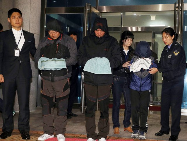 Lee Joon-seok, third from left, the captain of the ferry Sewol that sank off South Korea, and two crew members prepare to leave a court which issued their arrest warrant in Mokpo, south of Seoul, South Korea, Saturday, April 19, 2014. The captain of the sunken ferry, leaving more than 300 missing or dead, was arrested early Saturday on suspicion of negligence and abandoning people in need. (Photo by AP Photo/Yonhap)
