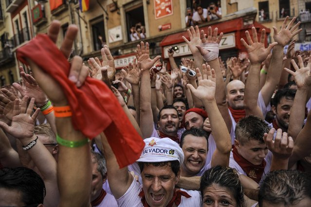 """Revelers celebrate during the launch of the """"Chupinazo"""" rocket, to celebrate the official opening of the 2015 San Fermin Fiestas, in Pamplona, northern Spain, Monday, July 6, 2015. (Photo by Alvaro Barrientos/AP Photo)"""