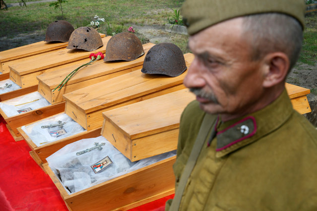 """A member of Ukrainian search organisation """"Pamyat"""" (Memory) stands next to coffins with remains of Red Army soldiers killed in World War Two, during a reburial ceremony in the village of Yurivka, outside Kiev, Ukraine, May 9, 2016. (Photo by Valentyn Ogirenko/Reuters)"""