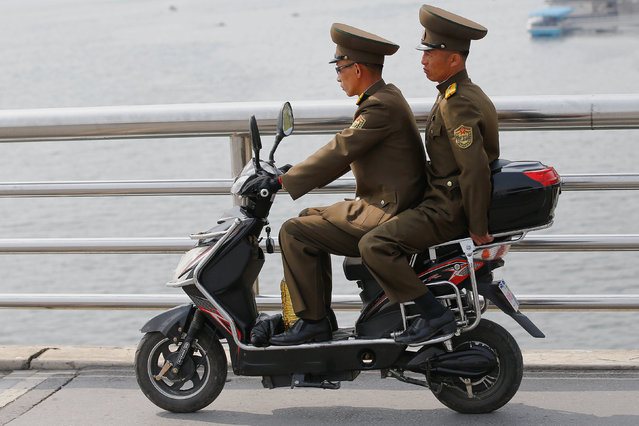 Soldiers cross the bridge on an electric scooter in central Pyongyang, North Korea April 16, 2017. (Photo by Damir Sagolj/Reuters)
