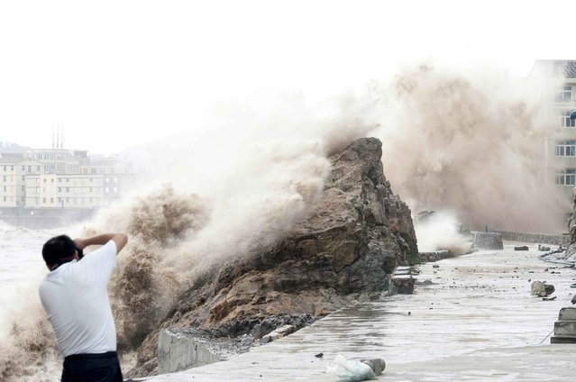 A man takes a photograph of huge waves as typhoon Chan-hom comes near Wenling, east China's Zhejiang province on July 10, 2015. (Photo by AFP Photo)