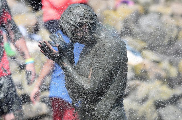 """A player gets a shower after her match at the so called """"Wattoluempiade"""" (Mud Olympics) in Brunsbuettel at the North Sea, July 11, 2015. (Photo by Fabian Bimmer/Reuters)"""
