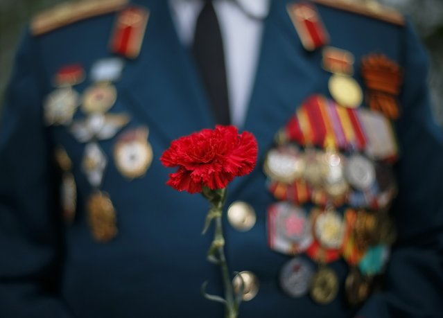 A former Soviet serviceman holds a carnation as he attends a wreath laying ceremony at a World War Two memorial during the celebrations marking Victory Day, in the Black Sea port of Odessa May 9, 2014. Ukraine celebrates the 1945 victory over Nazi Germany during World War Two on May 9. (Photo by Gleb Garanich/Reuters)