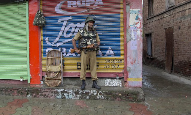 An Indian paramilitary soldier stands guard outside a closed market during a curfew in Srinagar, Indian controlled Kashmir, Monday, July 13, 2015. Parts of Indian-controlled Kashmir remained under curfew to stop a rally by separatist groups in memory of the day in 1931 when the region's Hindu king ordered more than 20 Kashmiri Muslims executed in a bid to put down an uprising. July 13 is observed as Martyrs' Day in the state. (Photo by Dar Yasin/AP Photo)
