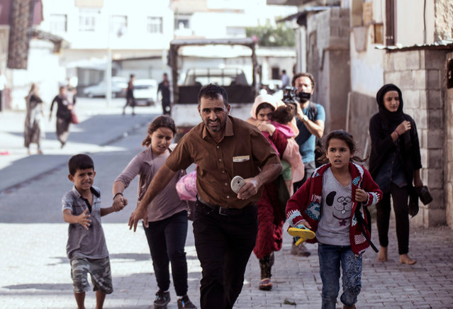 People run to take cover after mortars fired from Syria, in Akcakale, Turkey, Thursday, October 10, 2019. An Associated Press journalist said at least two government buildings were hit by the mortars in Sanliurfa province's border town of Akcakale and at least two people were wounded. (Photo by Ismail Coskun/IHA via AP Photo)