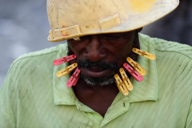 Plastic clothes pins are clipped to the skin of a dominos player, the punishment for losing team, as men compete in the game in Cite Soleil neighborhood of Port-au-Prince, Haiti, Thursday, October 10, 2019. Residents of Cite Soleil say that their already limited access to basic services, work, and security has only been declining, and many are participating in the protests calling for the resignation of President Jovenel Moise. (Photo by Rebecca Blackwell/AP Photo)