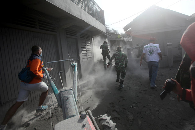 Rescuers rush to help villagers to evacuate their homes following the eruption of Mt. Sinabung in Gamber village, North Sumatra, Indonesia, Sunday, May 22, 2016. The volcano in western Indonesian unleashed hot clouds of ash on Saturday, killing several villagers, an official said. (Photo by Binsar Bakkara/AP Photo)