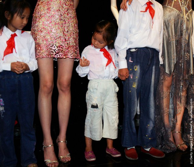 A student from impoverished families, whose education fees are sponsored by lingerie brand Aimer, views the skirt of a model as they welcome visitors with models at a charity lingerie show of Aimer