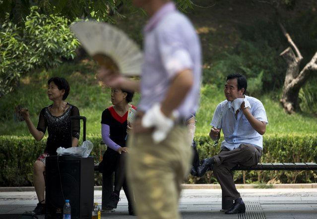 A man wipes his sweat next to women who use fans to cool themselves as they watch people perform social dance at Tuanjiehu Park in Beijing Sunday, July 12, 2015. (Photo by Andy Wong/AP Photo)