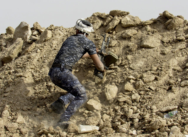 An Iraqi Federal policeman perches on a berm outside Fallujah, 40 miles (65 kilometers) west of Baghdad, Iraq, Tuesday, May 24, 2016. (Photo by Rwa Faisal/AP Photo)