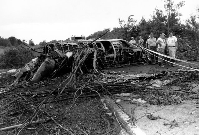 Rescue workers inspect the wreckage of a Cessna Citation airplane in Akron, Ohio, on August 2, 1979.  New York Yankees catcher Thurman Munson, piloting the plane, was killed in the crash. Two passengers survived. (Photo by Madeline Drexler/AP Photo)