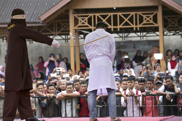 In this Monday, March 20, 2017, file photo, a Sharia law official whips a man convicted of adultery with a rattan cane in Banda Aceh, Indonesia, when two men each face up to 100 stroke of the cane after neighbors reported them to Islamic religious police for having gay s*x. Indonesian police detained dozens of men Sunday, May 21 in a weekend raid on a gay sauna in the capital Jakarta, another sign of growing hostility to homosexuality in the world's most populous Muslim nation. (Photo by Heri Juanda/AP Photo)
