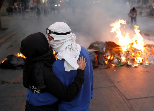 A masked couple of demonstrators kiss in front of a burning barricade during a protest against Chile's government in Santiago, Chile on November 25, 2019. (Photo by Goran Tomasevic/Reuters)