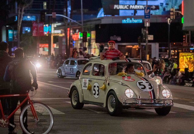 """Cars from the """"Herbie"""" movies are driven down Sunset Blvd during the 88th annual Hollywood Christmas Parade in Hollywood, California on December 1, 2019. (Photo by Mark Ralston/AFP Photo)"""