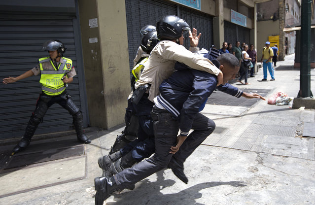 A National Bolivarian Police officer rescues a man who was being attacked by protesters, who then threw rocks at them, during a protest demanding food a few blocks from Miraflores presidential palace in Caracas, Venezuela, Thursday, June 2, 2016. (Photo by Fernando Llano/AP Photo)
