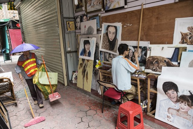A cleaner moves through the alleyways of the Defan village in Shenzhen as an artist creates paintings from photographs on June 12, 2014 in Shenzhen, China. The Dafen Artist Village in Guangdong province, China, is home to thousands of artists who reproduce some of the world's most iconic paintings as well as create their own works. The village, on the outskirts of Shenzhen, is becoming a major center for original Chinese art. (Photo by Palani Mohan/Getty images)