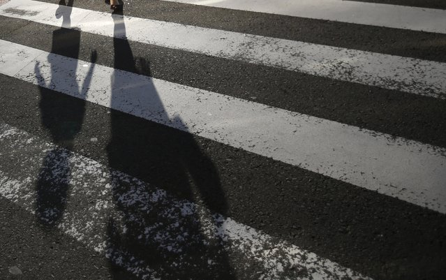 A mother and daughter cast shadows on a street crossing in Nagasaki, southwestern Japan, July 31, 2015. (Photo by Issei Kato/Reuters)