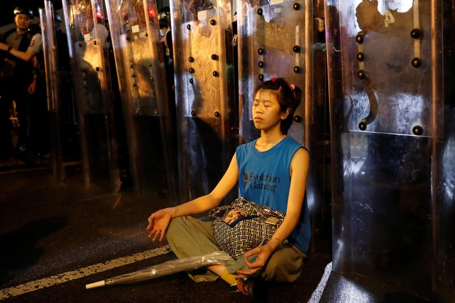 A demonstrator sits down in front of riot police during a demonstration to demand authorities scrap a proposed extradition bill with China, in Hong Kong, China on June 12, 2019. (Photo by Tyrone Siu/Reuters)