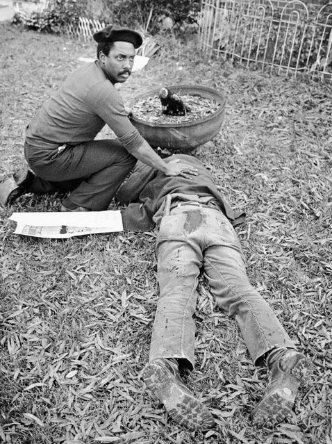 "In this November 3, 1979 file photo, Workers Viewpoint Organization member Nelson Johnson kneels by victim in aftermath of shooting in Greensboro, N.C.  The state, with the blessing of the Greensboro City Council, will use the word ""massacre"" for a highway historical marker commemorating the deaths of five Communist Workers Party members during a confrontation with Ku Klux Klansmen and the American Nazi Party. (Photo by Jim Stratford /News & Record via AP Photo)"