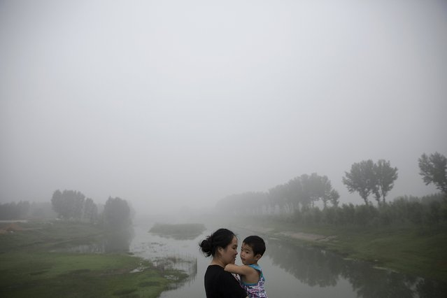 A woman holds a child as travellers wait for the highway from Beijing to China's Hebei Province to reopen after in was closed due to low visibility, on a heavy polluted morning August 3, 2015. (Photo by Damir Sagolj/Reuters)