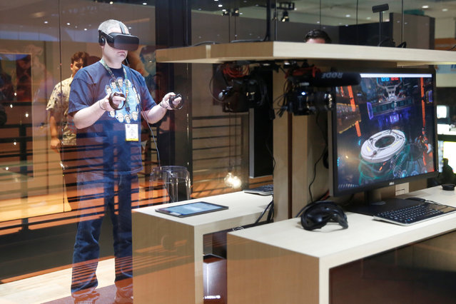 A man plays a frisbee throwing video game with the Oculus Rift VR headset at the E3 Electronic Expo in Los Angeles, California, U.S. June 14, 2016. (Photo by Lucy Nicholson/Reuters)