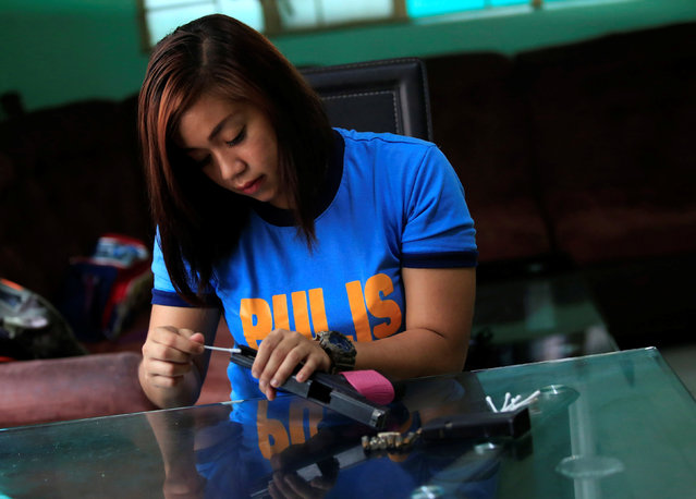 Aurea Jane Manalaysay, a member of the Philippine National Police Special Reaction Unit cleans a pistol during a day off at her home in Tondo city, metro Manila, Philippines May 29, 2016. (Photo by Romeo Ranoco/Reuters)