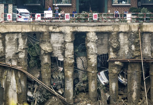 Cars are seen in a sunken open-air parking lot after heavy rainfall hit Chengdu, Sichuan province, July 9, 2014. Four cars fell into the pit and one was left stuck on the edge of a railing as the ground sunk, according to local media. (Photo by Reuters/China Daily)