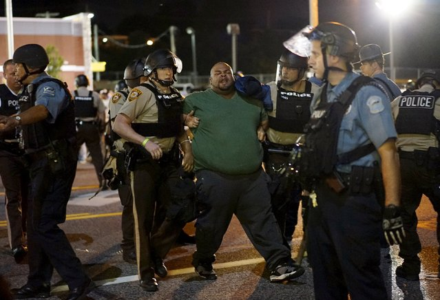 Police hold a protester who was detained in Ferguson, Missouri, August 10, 2015. Protesters regrouped in Ferguson, Missouri, on Monday evening after a state of emergency was declared, aimed at preventing a repeat of violence the night before on the anniversary of the police shooting of unarmed black man Michael Brown. (Photo by Rick Wilking/Reuters)